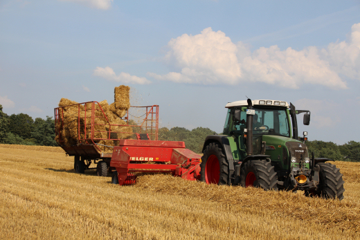 Traktor mit Ballenpresse auf Strohfeld